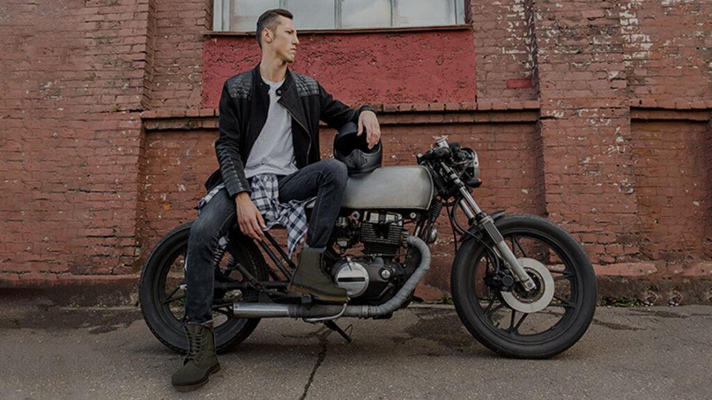 Fotografía joven vestido estilo grunge sentado en una motocicleta